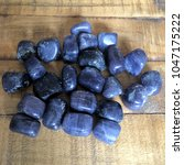 blue iolite tumbled crystals on ... | Shutterstock . vector #1047175222