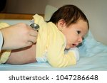 newborn child with a doctor | Shutterstock . vector #1047286648