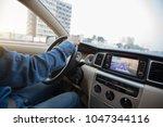 hands on wheel driving car in... | Shutterstock . vector #1047344116