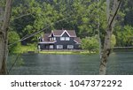 a lake house between the trees...   Shutterstock . vector #1047372292