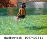 child playing in a pool of... | Shutterstock . vector #1047403516