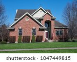 red brick house with tall... | Shutterstock . vector #1047449815