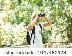 tourists man with binoculars... | Shutterstock . vector #1047482128