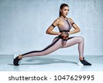 sporty woman doing lunges with... | Shutterstock . vector #1047629995