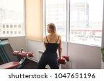 blonde girl posing in the gym.... | Shutterstock . vector #1047651196