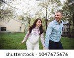 happy couple hold hands running ... | Shutterstock . vector #1047675676