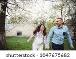 happy couple hold hands running ... | Shutterstock . vector #1047675682