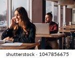 happy businesswoman sitting at... | Shutterstock . vector #1047856675