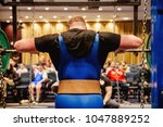 Small photo of back powerlifter in belt approach squat in competition powerlifting