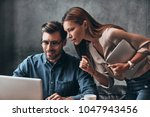discussing business. two young... | Shutterstock . vector #1047943456