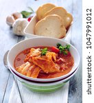 fish stew with tomato. | Shutterstock . vector #1047991012