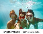cheerful women friends swimming ... | Shutterstock . vector #1048137238