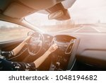 Young woman driving a car and adjusting car audio. Music in a car. Sunny day. Modern car interior - stock photo