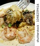 Small photo of Fettucini Alfredo pasta on the fork, with shrimp and mushroom on the side