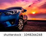 Stock photo blue compact suv car with sport and modern design parked on concrete road by the sea at sunset 1048266268