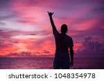 a young man is standing on the... | Shutterstock . vector #1048354978