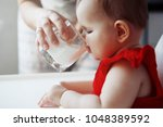 a cute baby in a red dress with ... | Shutterstock . vector #1048389592