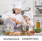 girl and her mother are cooking ... | Shutterstock . vector #1048397692