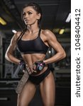 the girl in the gym crouches... | Shutterstock . vector #1048404412