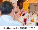 banquet guests applaud  the men'... | Shutterstock . vector #1048418212