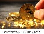 man holding golden bitcoin over ... | Shutterstock . vector #1048421245