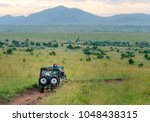 africa safari jeep driving on... | Shutterstock . vector #1048438315