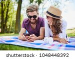 loving young couple using phone ... | Shutterstock . vector #1048448392