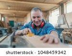 man doing woodwork in carpentry.... | Shutterstock . vector #1048459342