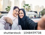 arabic women shopping outdoors... | Shutterstock . vector #1048459738