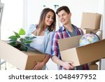 a couple with boxes moves to a... | Shutterstock . vector #1048497952