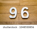 Small photo of Figures ninety-six on a wooden, parquet floor as a background.