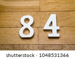Small photo of Figures eighty-four on a wooden, parquet floor as a background.
