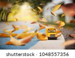 Small photo of Yellow school bus coming through the trees tunnel with autumn leaves.