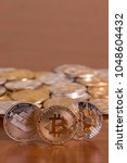Small photo of several aligned crypto currency coins on top of wooden table.
