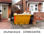 Small photo of Yellow rubbish skip, on a driveway, next to house, England.