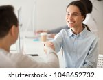 Small photo of Happy hired intern, successful student, promoted woman employee smiling shaking boss hand congratulating worker for good work result, appreciating supporting young motivated professional by handshake