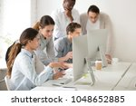 Small photo of Executive mentor explaining intern or new employee online task pointing at computer screen, female boss supervisor teaching young girl to use corporate software or helping with difficult assignment