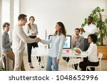 boss shaking hand of young shy... | Shutterstock . vector #1048652996