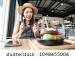 young asian woman eating... | Shutterstock . vector #1048655006