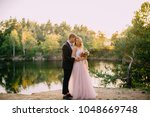 groom kisses a happy bride... | Shutterstock . vector #1048669748