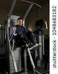 Small photo of Contemporary sportsman in activewear sitting on cross training equipment and pumping arm muscles