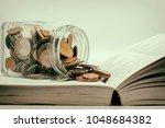 glass jar of coin on a book... | Shutterstock . vector #1048684382