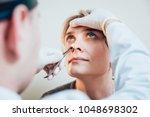 otolaryngologist examines woman'... | Shutterstock . vector #1048698302