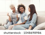 diverse female friends at home. ... | Shutterstock . vector #1048698986