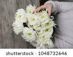 close up of flowers in hands of ... | Shutterstock . vector #1048732646