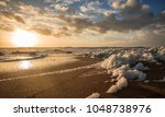 sea foam  on the beach at sunset | Shutterstock . vector #1048738976