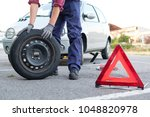 man changing a flat tyre after... | Shutterstock . vector #1048820978