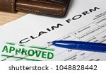 claim form on a wooden surface. ... | Shutterstock . vector #1048828442