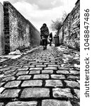 Small photo of UK northern alleyway with two females walking past garbage cans. Cobblestone pathway. Black and white