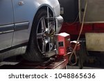 Small photo of Tire clamped with aligner auto wheel alignment in garage